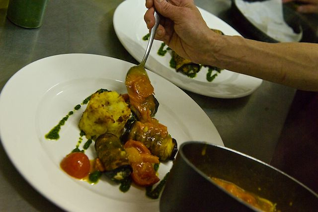Chef assembling a plate of food.