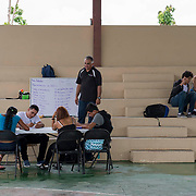 Punta Santiago, PR--Yamil Esquilin teaches Physics in the outdoor basketball court at the Programa de EducaciÛn Comunal de Entrega y Servicio (P.E.C.E.S.) school. The school's building was damaged during Hurricane Maria, so the school has been holding it's classes outdoors for over a month. Photo by Lori Waselchuk/BRAF