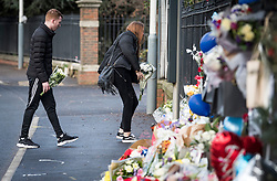 © Licensed to London News Pictures. 28/01/2018. London, UK. A young couple place flowers at the scene where three teenage pedestrians were killed near a bus stop in Hayes, West London after a black Audi collided with them. Named locally as Harry Rice, Josh Kennedy and George Wilkinson, the three teenagers were hit on Friday night  close to the M4 Junction 4. A 28-year-old man has been arrested and a police are currently looking for a  second man believed to have been in the Audi.. Photo credit: Ben Cawthra/LNP