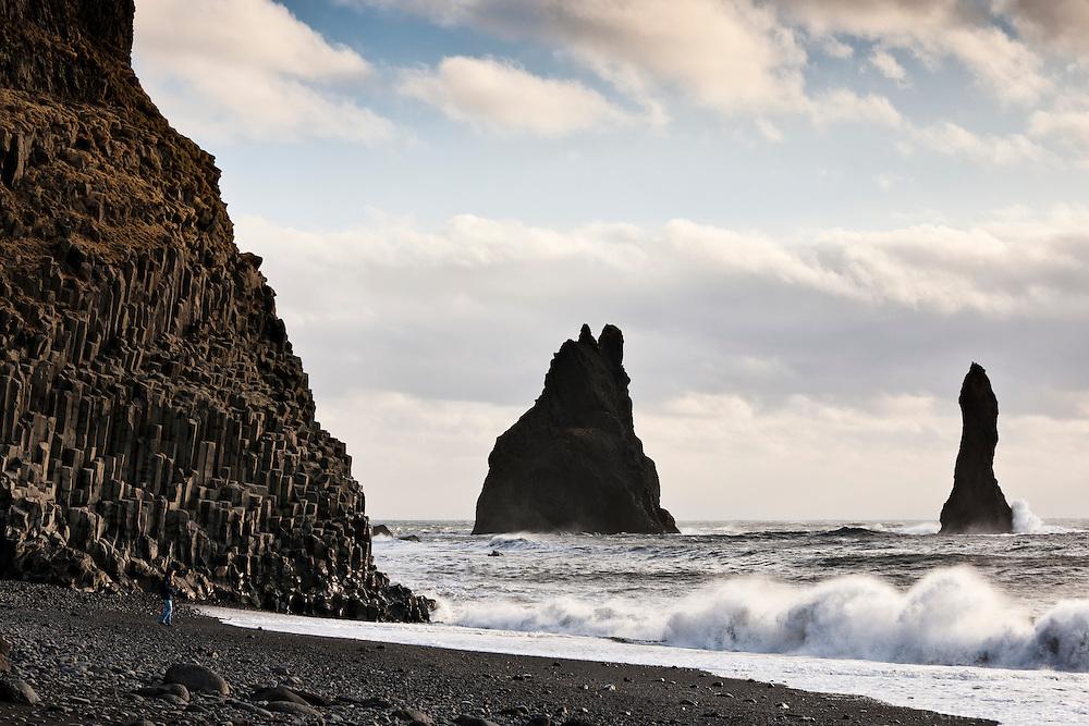 Reynisfjara black sand beach, south shore Iceland. Sea stacks in background. Woman standing on beach.