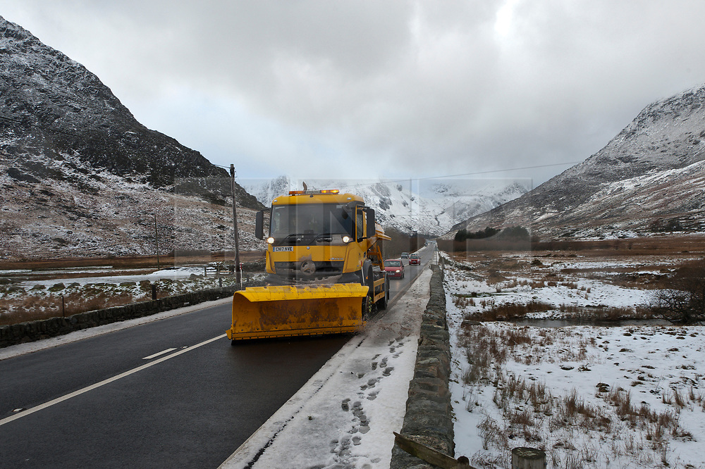 © Licensed to London News Pictures. 22/01/2019. Snowdonia, Gwynedd, Wales, UK. A gritter truck works along the A5 road surrounded by a bleak wintry landscape as showers of sleet, snow and hail continue in Snowdonia National Park, Gwynedd, Wales, UK. credit: Graham M. Lawrence/LNP