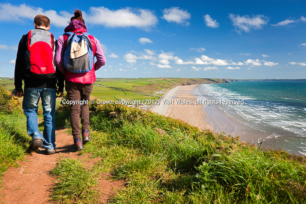 Couple walking on Coast Path with Newgale beach in distance <br /> St Bride's Bay<br /> Pembrokeshire<br /> South<br /> Walking<br /> Activities and Sports