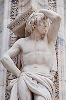 Milan, Italy, Duomo Cathedral. Stone statue of a handsome man bearing a pedestal.