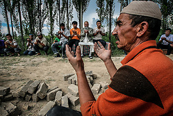 Uzbek men pray as they buried a woman killed in the ethnic clashes in Osh, Kyrgyzstan, 15 June 2010. According to media reports 176 people were killed and 1700 wounded during the ethnic clashes in Kyrgyzstan during past days.