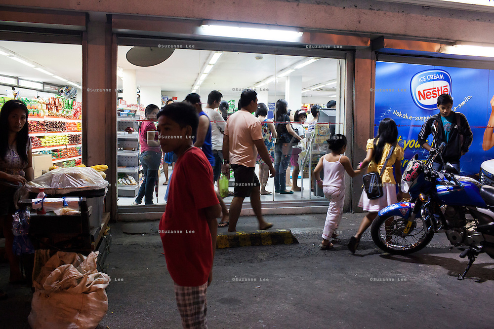 People queue up to pay in a pharmacy and drug store in Paranaque, Metro Manila, The Philippines on 19 January 2013. Photo by Suzanne Lee for Save the Children UK