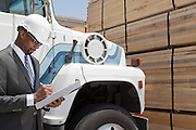 African American male contractor writing notes while standing by logging truck