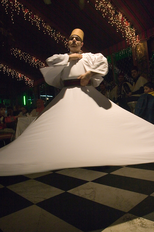 The Melaweieh dance performance in a Restaurant in Damascus (Syria). This is an religious, mystic and spiritual dance. The dancer turns on himself (spins) leaning to one side or to the front 99 times to reach religious ecstasy. The Melaweieh dancer wears broad white clothes and a typical conical hat. <br /> Un hombre ejecuta el baile tradicional sirio en un restaurante de Damasco (Siria). El bailar&iacute;n ejecuta 99 giros a toda velocidad sobre si mismo, llegando hacia el final a un estado de comunicaci&oacute;n m&iacute;stica con Dios, seg&uacute;n cuenta la tradici&oacute;n.
