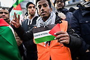 Frankfurt am Main | 16.12.2017<br /> <br /> On Saturday, December 16, 2017 about 1000 men, women and children take part in a demonstration march against the declaration of U.S. president Donald Trump to recognize Jerusalem as the capital of Israel and to relocate the U.S. Embassy in Israel from Tel Aviv to Jerusalem. The demonstration was registered under the slogan &quot;Demo f&uuml;r Jerusalem - Jerusalem/Alkudus ist die Hauptstadt Pal&auml;stinas&quot; (Demo for Jerusalem - Alkudus is the capital of Palestine).<br /> Here: A protester is holding a small flag of Palestine with the words &quot;Solidarity with Palestine&quot;.<br /> <br /> photo &copy; peter-juelich.com<br /> <br /> - Foto honorarpflichtig<br /> - No Model Release<br /> - No Property Release