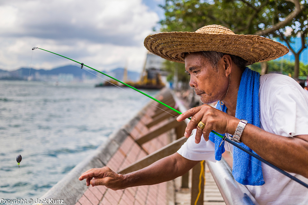 11 AUGUST 2013 - HONG KONG: A man fishes off the public waterfront esplanade at Kennedytown in Hong Kong. Hong Kong is one of the two Special Administrative Regions of the People's Republic of China, Macau is the other. It is situated on China's south coast and, enclosed by the Pearl River Delta and South China Sea, it is known for its skyline and deep natural harbour. Hong Kong is one of the most densely populated areas in the world, the  population is 93.6% ethnic Chinese and 6.4% from other groups. The Han Chinese majority originate mainly from the cities of Guangzhou and Taishan in the neighbouring Guangdong province.      PHOTO BY JACK KURTZ