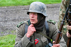 A world war two Re-enactor portraying a German panzer grenadier from the Grossdeutschland Division. He is wearing the two Medal Ribbons, Iron Cross 2nd Class (top) and the Ost front or Eastern Front Medal nicknamed the Cold Meat Medal. Under the iconic German Stahlhelm he is wearing a Toque or tubular woven head scarf, standard issue to all German troops and carrying a mauser K98 rifle.<br />