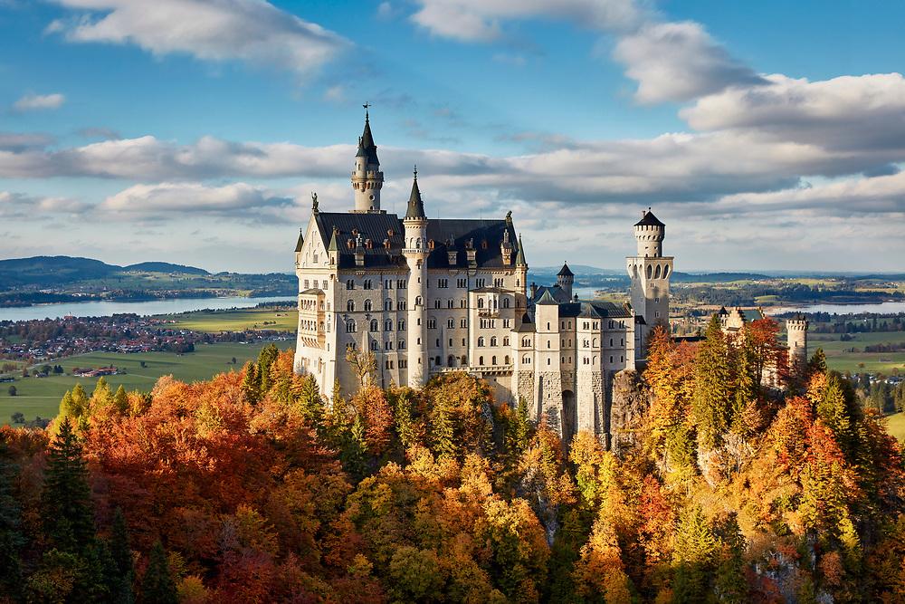 Schloss Neuschwanstein im herbstlichen Abendlicht, das König Ludwig II. ab 1869 auf einem zerklüfteten Felsen in malerischer Bergszenerie errichten ließ.