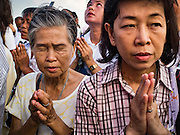 18 NOVEMBER 2015 - BANGKOK, THAILAND: People pray at the chedi at Wat Saket during the parade marking the start of the temple's annual fair. Wat Saket is on a man-made hill in the historic section of Bangkok. The temple has golden spire that is 260 feet high which was the highest point in Bangkok for more than 100 years. The temple construction began in the 1800s in the reign of King Rama III and was completed in the reign of King Rama IV. The annual temple fair is held on the 12th lunar month, for nine days around the November full moon. During the fair a red cloth (reminiscent of a monk's robe) is placed around the Golden Mount while the temple grounds hosts Thai traditional theatre, food stalls and traditional shows.      PHOTO BY JACK KURTZ