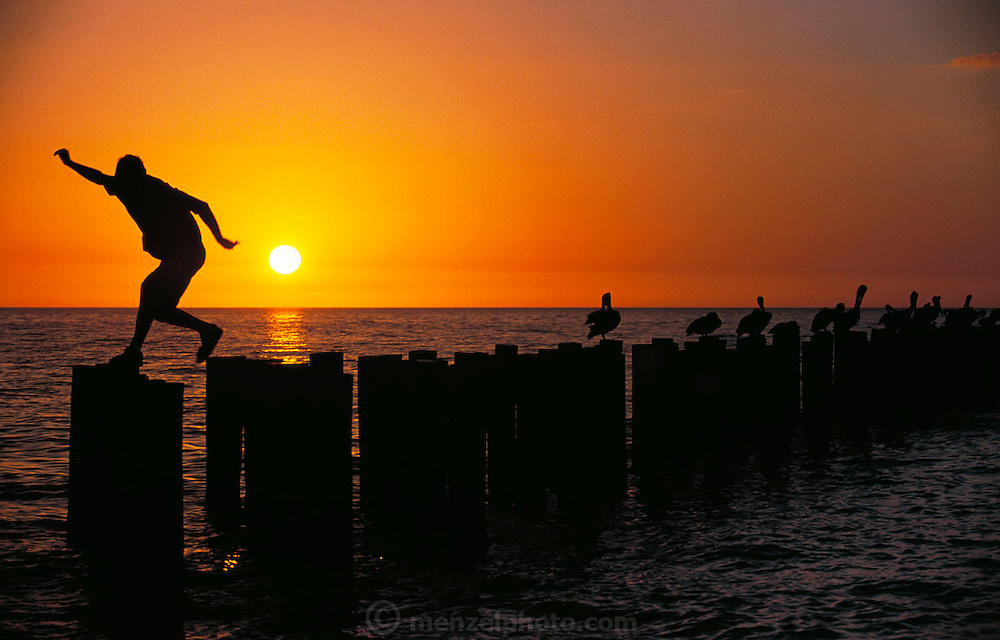 Young man jumps between pillars at sunset.  Naples, Florida, USA. MODEL RELEASED.