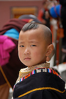 Young boy dressed in ceremonial garb -with snow leopard skin - in Zaru temple in Jiuzhaigou national park.