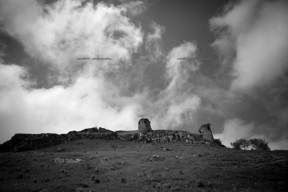 """Remainings of Shuhsis old fortress. This image is part of the photoproject """"The Twentieth Spring"""", a portrait of caucasian town Shushi 20 years after its so called """"Liberation"""" by armenian fighters. In its more than two centuries old history Shushi was ruled by different powers like armeniens, persians, russian or aseris. In 1991 a fierce battle for Karabakhs independence from Azerbaijan began. During the breakdown of Sowjet Union armenians didn´t want to stay within the Republic of Azerbaijan anymore. 1992 armenians manage to takeover """"ancient armenian Shushi"""" and pushed out remained aseris forces which had operate a rocket base there. Since then Shushi became an """"armenian town"""" again. Today, 20 yeras after statement of Karabakhs independence Shushi tries to find it´s opportunities for it´s future. The less populated town is still affected by devastation and ruins by it´s violent history. Life is mostly a daily struggle for the inhabitants to get expenses covered, caused by a lack of jobs and almost no perspective for a sustainable economic development. Shushi depends on donations by diaspora armenians. On the other hand those donations have made it possible to rebuild a cultural centre, recover new asphalt roads and other infrastructure. 20 years after Shushis fall into armenian hands Babies get born and people won´t never be under aseris rule again. The bloody early 1990´s civil war has moved into the trenches of the frontline 20 kilometer away from Shushi where it stuck since 1994. The karabakh conflict is still not solved and could turn to an open war every day. Nonetheless life goes on on the south caucasian rocky tip above mountainious region of Karabakh where Shushi enthrones ever since centuries."""