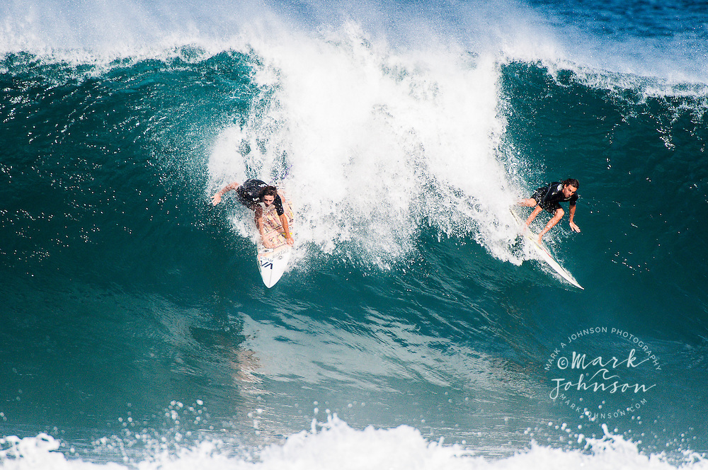 1 surfer going right, 1 surfer going left while surfing at the Banzai Pipeline, North Shore, Oahu, Hawaii