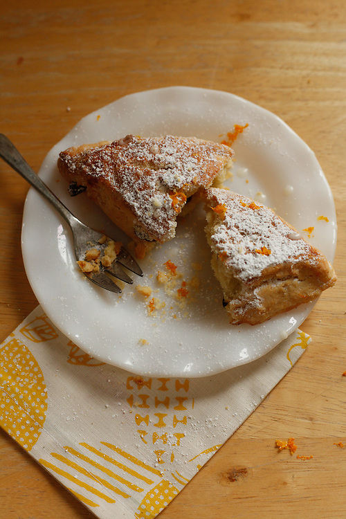 Orange-cranberry breakfast scones sprinkled with powdered sugar and glazed.