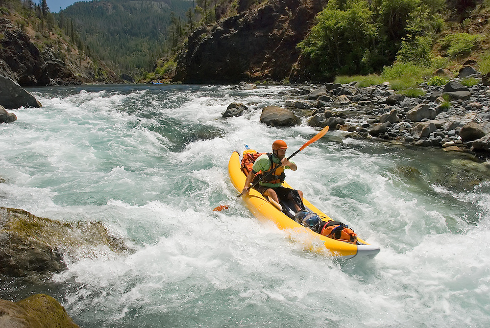 Paddling an inflatable kayak down a rapid on the Illinois River in Oregon's Siskiyou Mountains.