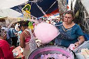 "A woman making cotton candy in Mixquic for Day of the Dead Celebrations. Mexicans visiting their dead relatives, lighting candles, lighting incense and decorating their graves for the Day of the Dead festival in San Andre de Mixquic shot as part of the Sony RX100 III ""Celebrate The Streets"" series."
