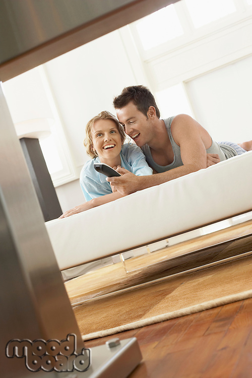 Couple on bed watching television together