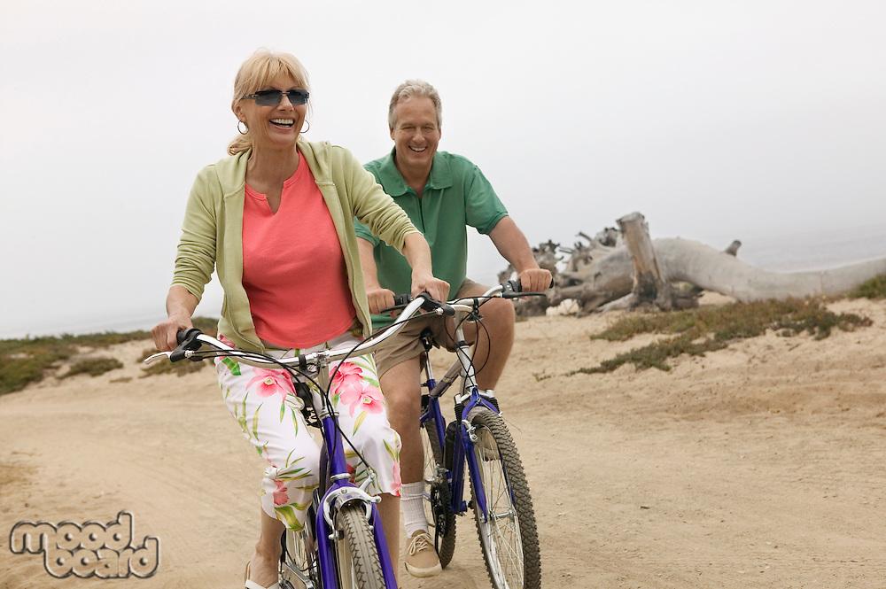 Couple riding bicycles along beach