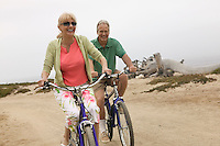Couple riding bicycles along beach