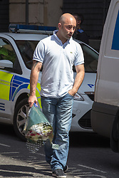 © Licensed to London News Pictures . 14/07/2013 . Manchester , UK . A man leaving flowers at the scene where a fire fighter, identified as Stephen Hunt, died while tackling a fire in a store-room of Paul's Hair World in Oldham Street, Manchester. Two 15-year-old girls arrested on suspicion of manslaughter. Photo credit : Joel Goodman/LNP