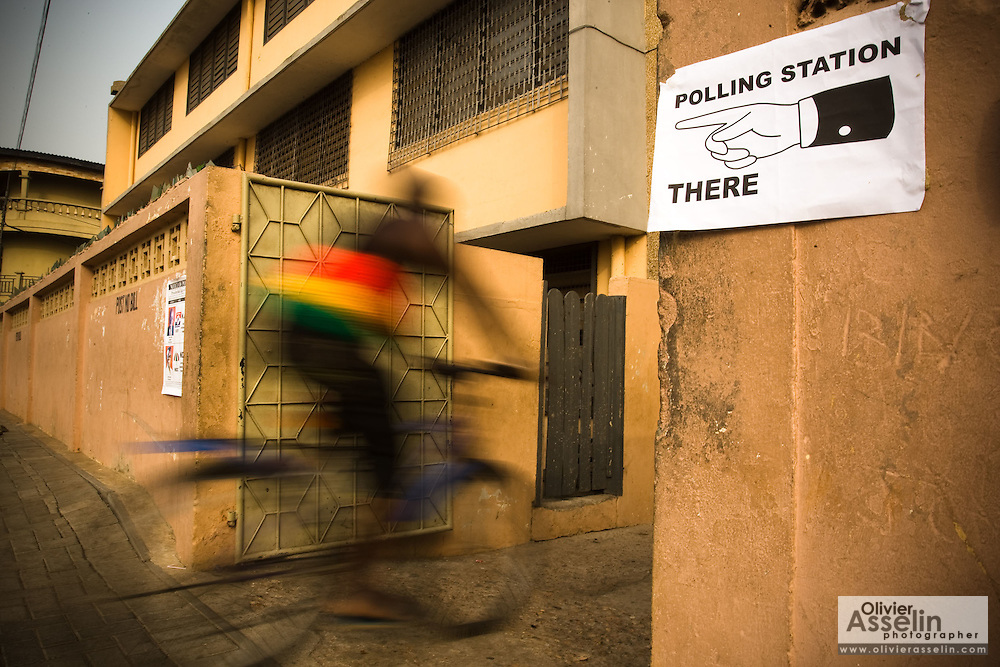 A man wearing a shirt in the colours of Ghana's national flag rides a bicycle into a polling station during presidential elections in Accra, Ghana on Sunday December 28, 2008. Voters were back at the polls to decide on a new leader after none of the candidates was able to obtain a 50 percent plus one vote majority during the election's first round on Dec 7.