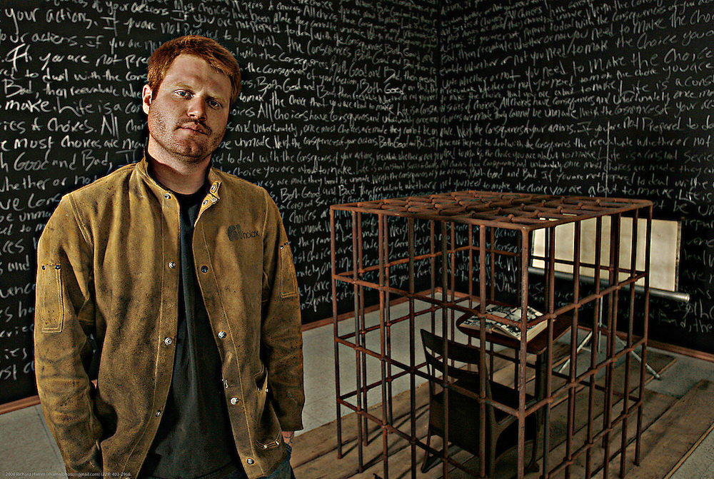 University of Georgia sculpture student George Morgan stands with his instillation piece at the Thomas Street Art Complex in Athens, Ga. on April 27, 2008. Morgan's piece pays homage to his views of the strict and restrictive school he attended before coming to the University, and is composed of several chalkboards scribed by a paragraph Morgan was often forced to write for countless hours of detention, a caged desk and an old John Deer Tractor chastity.