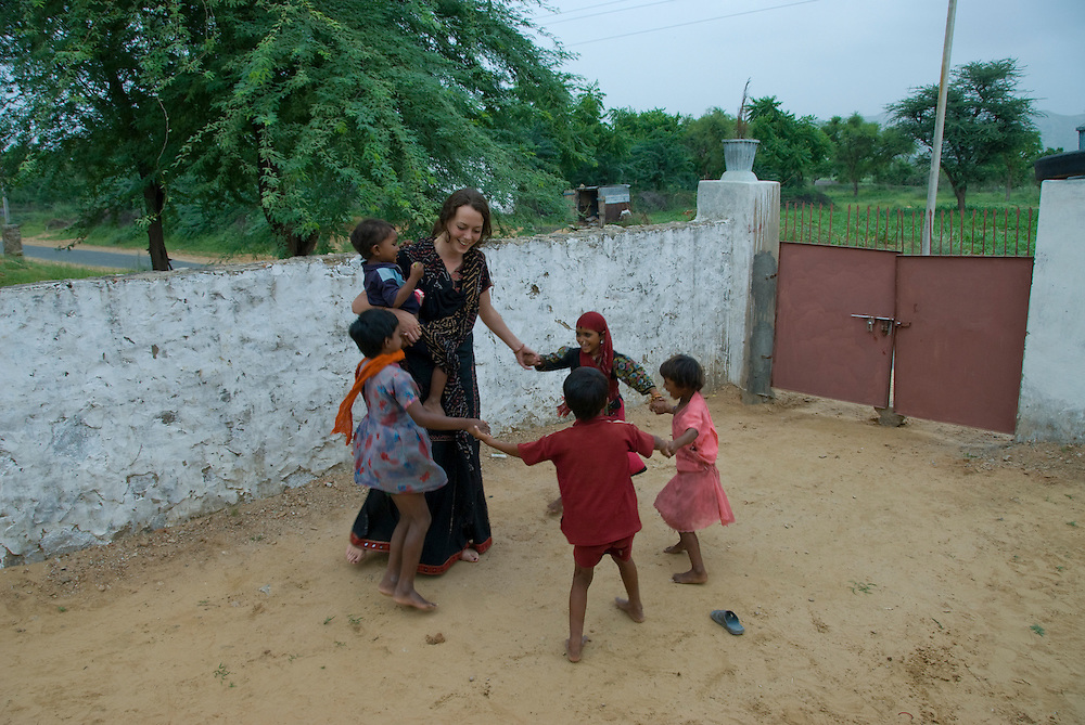 A young Western woman plays with local village children in the courtyard of a Rajasthani house (Thar desert, Rajasthan, India)