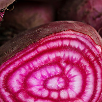 Chiogga beet sliced in half to show its characteristic red and white concentric candy-stripe.