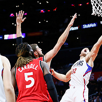 5 October 2016: Los Angeles Clippers forward Blake Griffin (32) goes for the layup past Toronto Raptors forward DeMarre Carroll (5) and Toronto Raptors center Jonas Valanciunas (17) during the Los Angeles Clippers 104-98 victory over the Toronto Raptors, at the Staples Center, Los Angeles, California, USA.