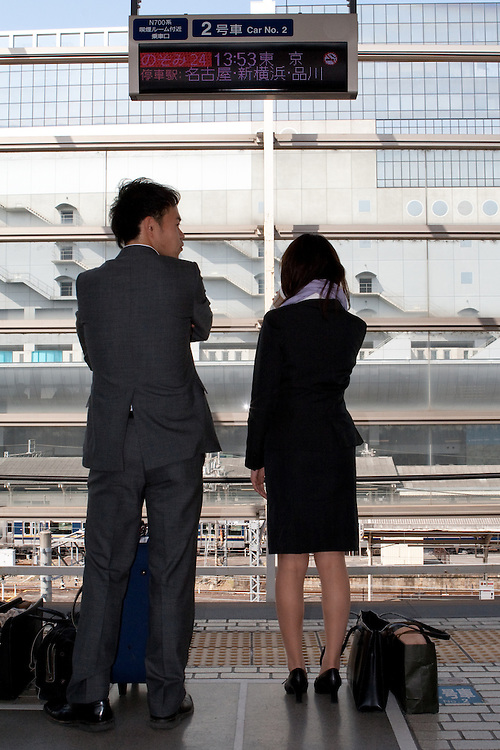 A couple wait for the Shinkasen bullet train in Osaka, Japan