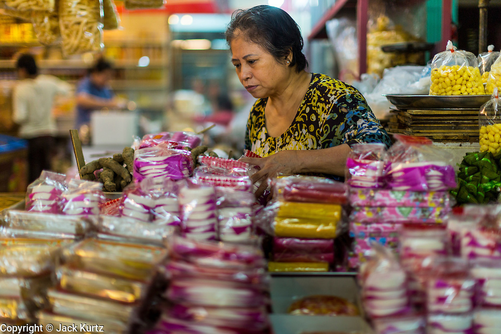 18 SEPTEMBER 2013 - BANGKOK, THAILAND: A mooncake vendor sells her wares in a market in the Chinatown section of Bangkok. Thailand in general, and Bangkok in particular, has a vibrant tradition of street food and eating on the run. In recent years, Bangkok's street food has become something of an international landmark and is being written about in glossy travel magazines and in the pages of the New York Times. Mooncake is a Chinese bakery product traditionally eaten during the Mid-Autumn Festival (Zhongqiu). The festival is for lunar worship and moon watching, when mooncakes are regarded as an indispensable delicacy. Mooncakes are offered between friends or on family gatherings while celebrating the festival. The Mid-Autumn Festival is one of the four most important Chinese festivals.      PHOTO BY JACK KURTZ