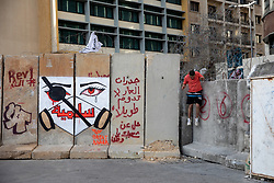 © Licensed to London News Pictures. 27/01/2020. Beirut, Lebanon. A man jumps down from a security barricade around the government buildings in Downtown Beirut, as the government votes on the 2020 budget. Anti government demonstrators have been campaigning against government corruption and economic crisis for 103 days in Lebanon. Photo credit : Tom Nicholson/LNP