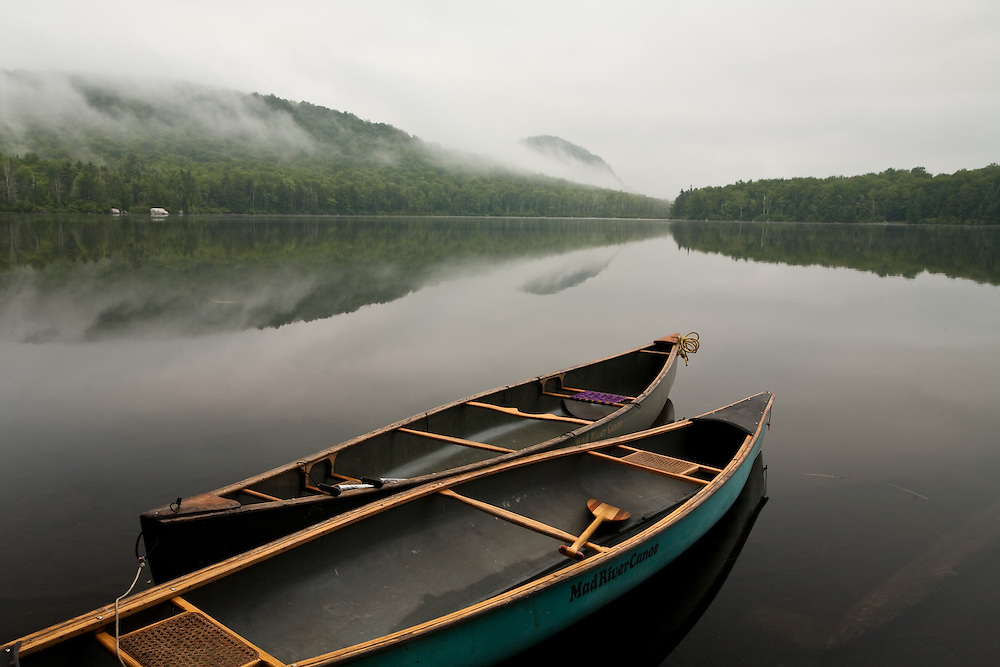 Low lying clouds shroud the hills around Kettle Pond in Groton State Forest, Vermont while canoes await paddlers.