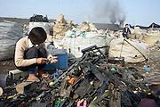 A migrant worker takes apart electronic trash in a junk yard in Longmen.