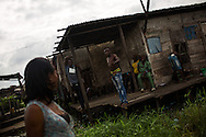 Bunmi Aiyenura, 23, turns to face a group of men catcalling her from a porch as she walks home, in the Badia neighborhood of Lagos, Nigeria, August 25, 2013.  Bunmi says she has had eight pregnancies by the same boyfriend-- seven of which ended in abortion-- and says she has not ever been educated about birth control.  The last pregnancy ended in miscarriage and her boyfriend, who was finally ready for a child, left her for her best friend.