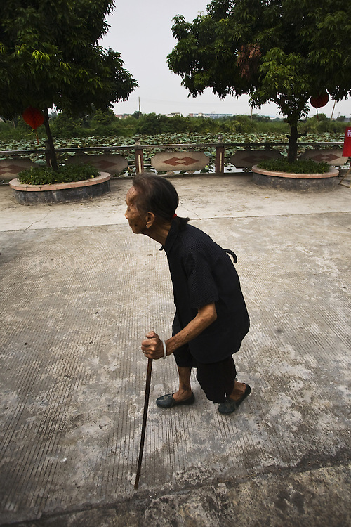 Old woman walks through Cha Tang Village, at Guangzhou periphery. Guangdong, China.