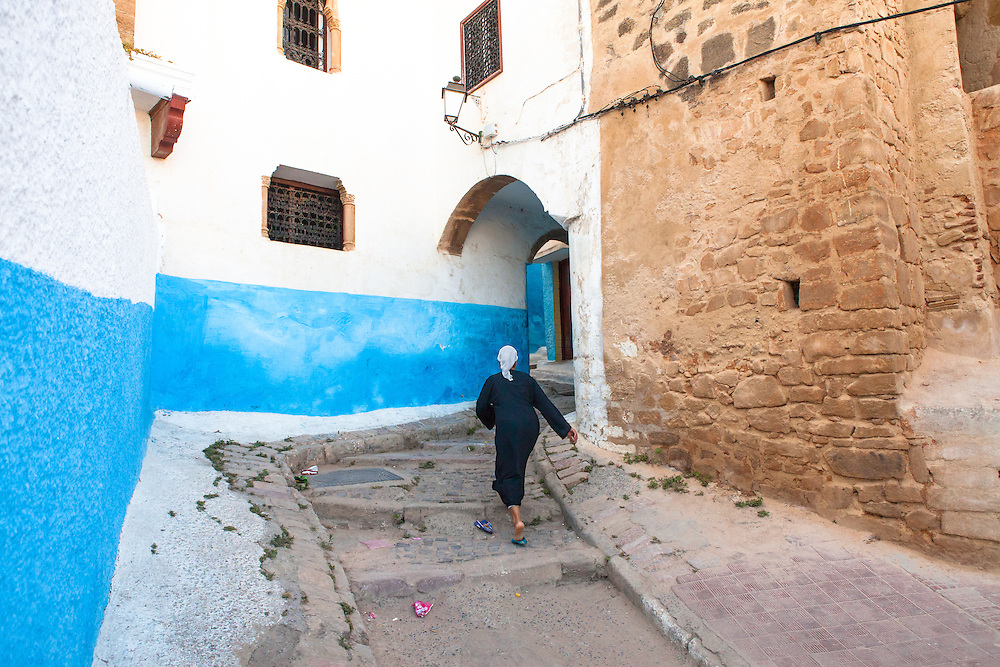 Muslim woman, wearing a traditional black djellaba and a white headscarf, at the Kasbah les Oudaias, the oldest part of Rabat, the capital of Morocco.