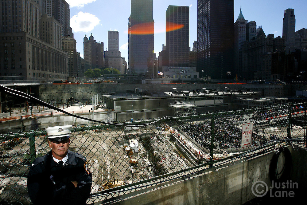 A New York City firefighter (L) stands at the edge of ground zero as family members (bottom R) gather at the edge of one of two reflecting pools marking the locations of the World Trade Center towers during the September 11th commemoration ceremony in New York on Monday 11 September 2006. This year marks the five year anniversary of the attacks. ..