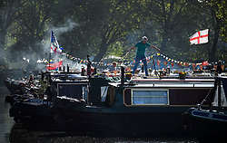 © Licensed to London News Pictures. 04/05/2019. London, UK. A canal boat owner puts bunting up on his boat during the Canalway Cavalcade festival in Little Venice, West London on Saturday, May 4th 2019. Inland Waterways Association's annual gathering of canal boats brings around 130 decorated boats together in Little Venice's canals on May bank holiday weekend. Photo credit: Ben Cawthra/LNP