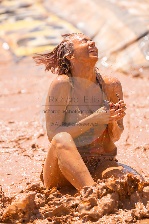 A young woman slips down a mud slide during the 2015 National Red Neck Championships May 2, 2015 in Augusta, Georgia. Hundreds of people joined in a day of country sport and activities.