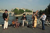 1997, Paris, France --- Street Musicians Playing near the Water --- Image by © Owen Franken/CORBIS