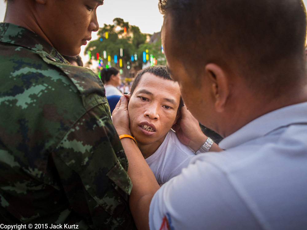 "07 MARCH 2015 - NAKHON CHAI SI, NAKHON PATHOM, THAILAND: Soldiers bring a man out of a trance after he charged the stage at the Wat Bang Phra tattoo festival. Wat Bang Phra is the best known ""Sak Yant"" tattoo temple in Thailand. It's located in Nakhon Pathom province, about 40 miles from Bangkok. The tattoos are given with hollow stainless steel needles and are thought to possess magical powers of protection. The tattoos, which are given by Buddhist monks, are popular with soldiers, policeman and gangsters, people who generally live in harm's way. The tattoo must be activated to remain powerful and the annual Wai Khru Ceremony (tattoo festival) at the temple draws thousands of devotees who come to the temple to activate or renew the tattoos. People go into trance like states and then assume the personality of their tattoo, so people with tiger tattoos assume the personality of a tiger, people with monkey tattoos take on the personality of a monkey and so on. In recent years the tattoo festival has become popular with tourists who make the trip to Nakorn Pathom province to see a side of ""exotic"" Thailand.   PHOTO BY JACK KURTZ"