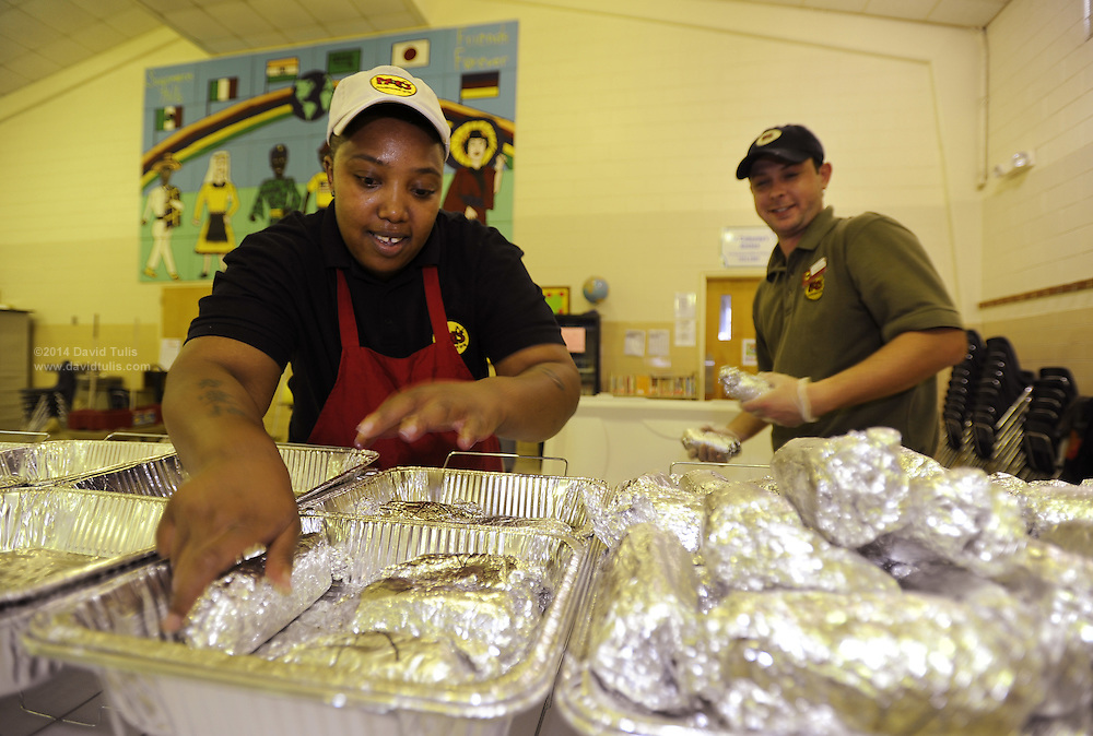 Moe's Burritos employees Ree, left, and Tom prepare over 100 burritos where Sagamore Hills Elementary School students and their parents participate in a family dinner and bingo event in Atlanta, on Tuesday, Sept. 13, 2011.    (David Tulis/dtulis@gmail.com)