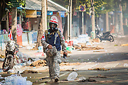 26 DECEMBER 2013 - BANGKOK, THAILAND: A volunteer medic helping anti-government protestors walk down a street in front of the Thai-Japan Stadium and Ministry of Labour, scene of fighting between police and rioters, during a lull in the fighting. Thousands of anti-government protestors flooded into the area around the Thai Japan Stadium to try to prevent the drawing of ballot list numbers by the Election Commission, which determines the order in which candidates appear on the ballot of the Feb. 2 election. They were unable to break into the stadium and ballot list draw went as scheduled. The protestors then started throwing rocks and small explosives at police who responded with tear gas and rubber bullets. At least 20 people were hospitalized in the melee and one policeman was reportedly shot by anti-government protestors.      PHOTO BY JACK KURTZ