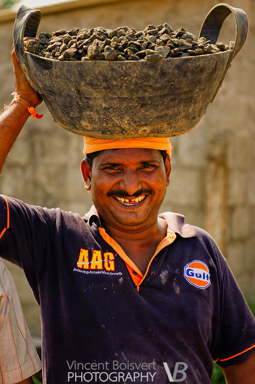 a smiling south indian man carrying heavy loads of crushed stone for a concrete mix