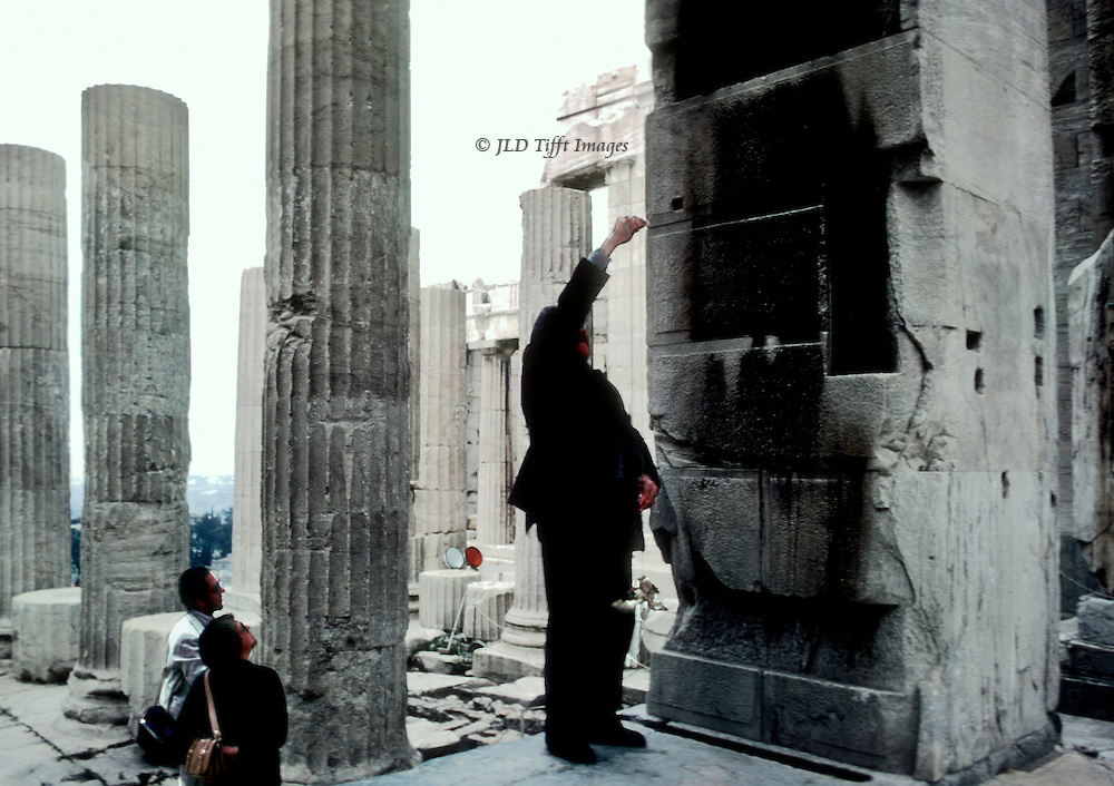 An Acropolis restoration supervisor checks verticality of a Propylon support with a plumb bob, while a couple of tourists watch from below.