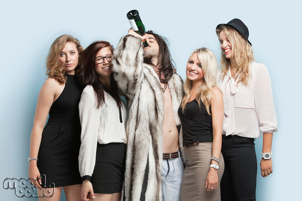 Young man drinking beer while standing with female friends against light blue background